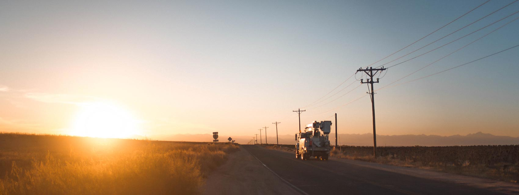 Truck driving down road in sunrise