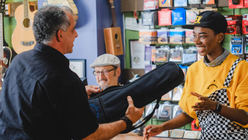 Man handing music instrument to lady in shop