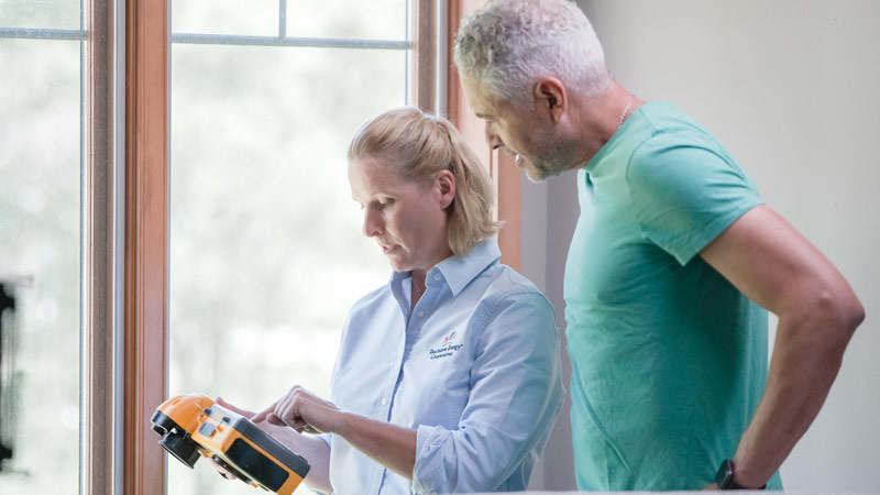 Man and woman checking energy measuring device